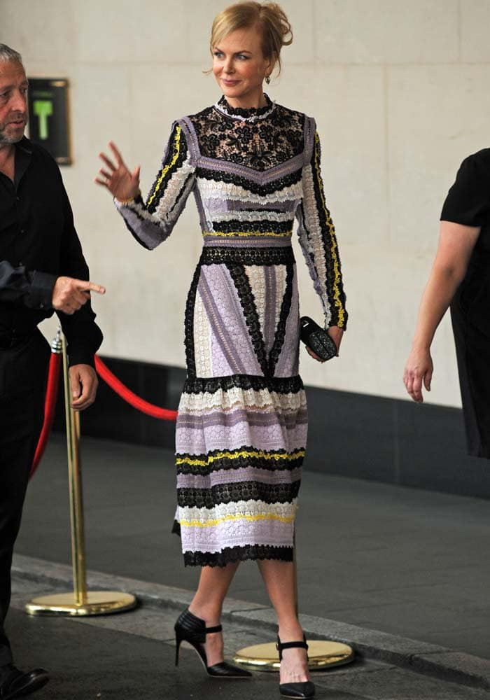 Nicole Kidman smiles and waves while wearing a purple, black, white and yellow frock from Erdem