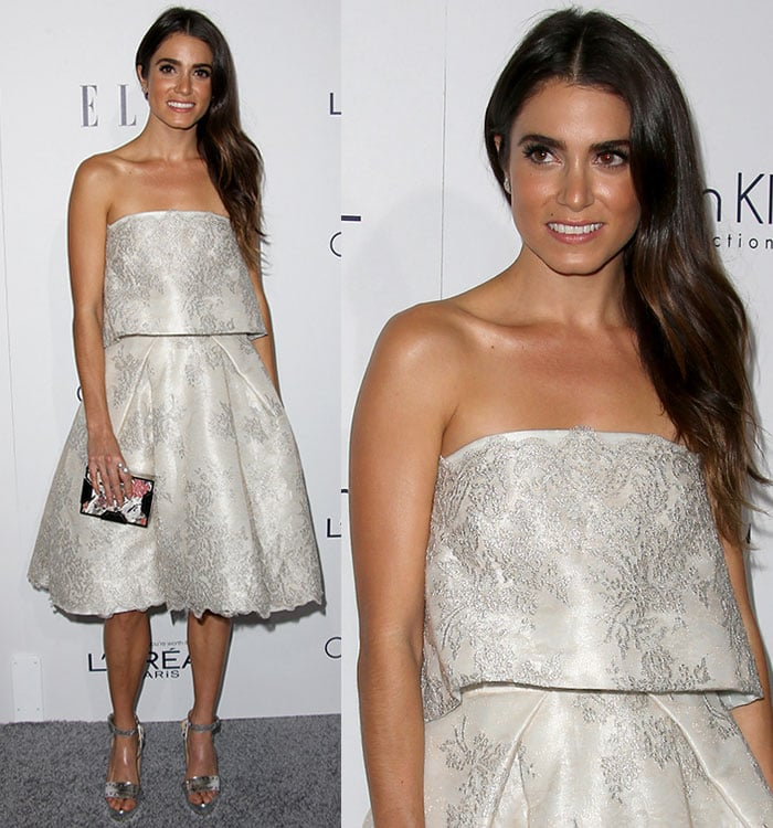 Nikki Reed wears her brown hair down and wavy as she poses for photos