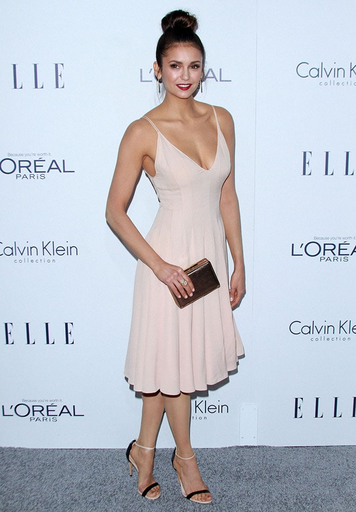 Nina Dobrev in a softly pleated dress by Calvin Klein featuring a cleavage-baring low-cut neckline, spaghetti straps, and a feminine A-line silhouette