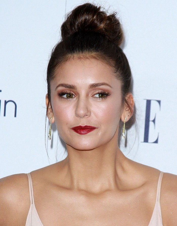 Nina Dobrev's hair was swept up into a high bun, while her face was gorgeously made up with a slick of red lipstick