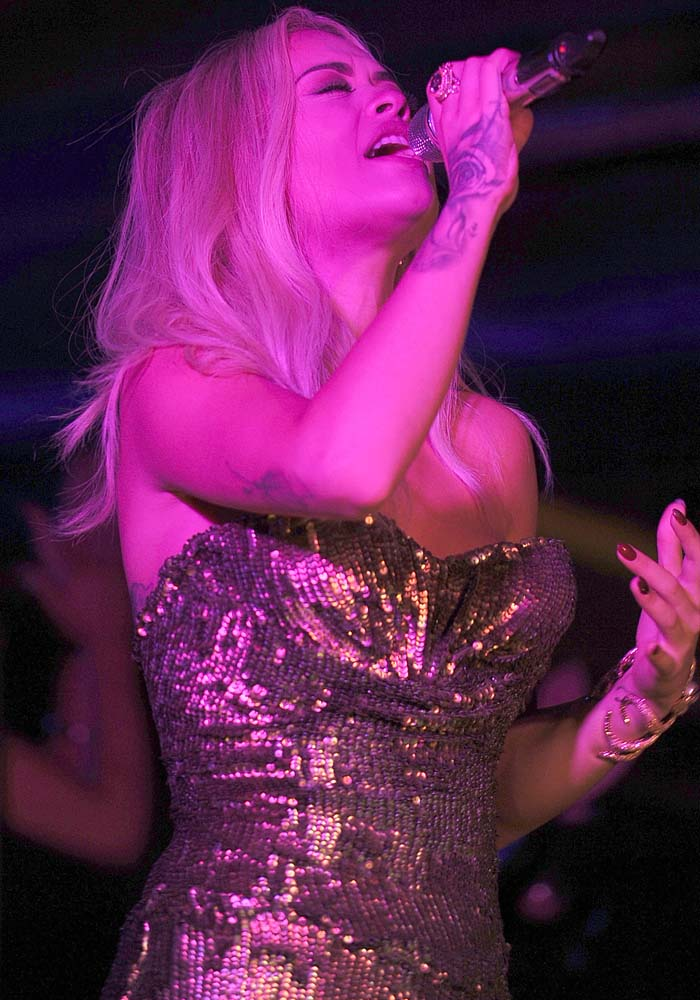 Rita Ora clutches a microphone and performs in a sparkling gold dress