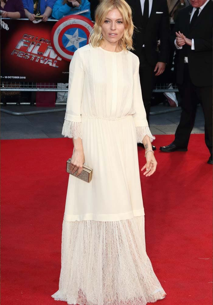 Sienna Miller awkwardly poses on the red carpet for the BFI London Film Festival