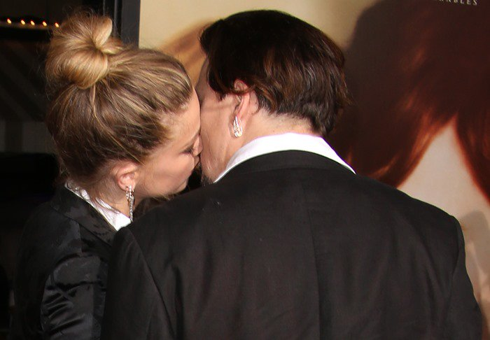 Johnny Depp gets a kiss from Amber Heard at the premiere of her movie The Danish Girl