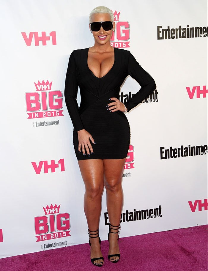 Amber Rose wore a fitted black bandeau LBD that features a plunging neckline, a back zipper fastening, and a thigh-grazing hem