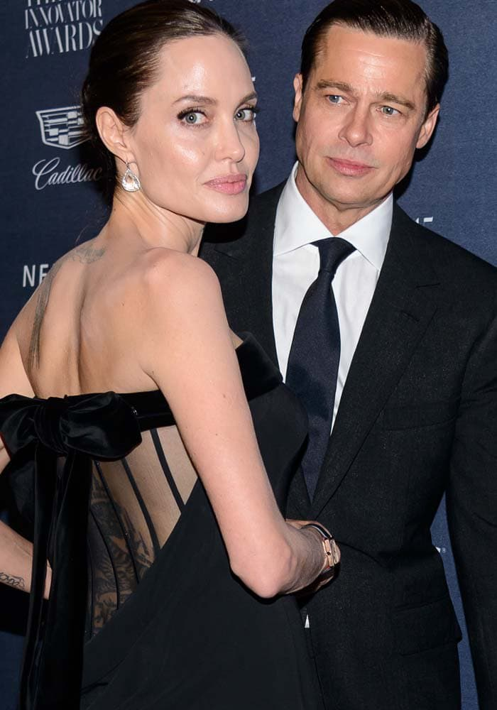 Angelina Jolie shows off her back tattoos as she faces husband Brad Pitt at the WSJ Magazine 2015 Innovator Awards