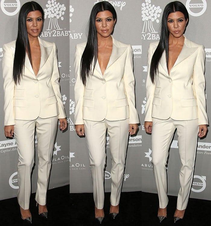 Kourtney Kardashian shows off her dark hair and tan skin in a cream Dolce & Gabbana pantsuit