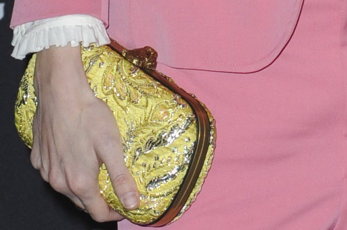 Brit Marling carries a yellow clutch in her unmanicured hands