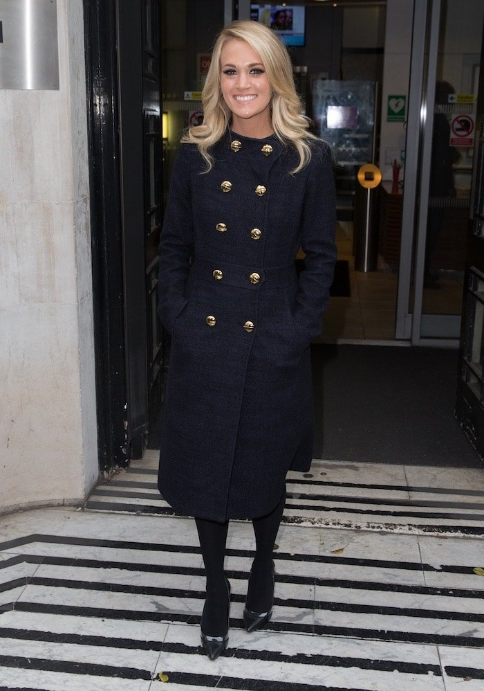 Carrie Underwood covers up in a long coat embellished with gold buttons