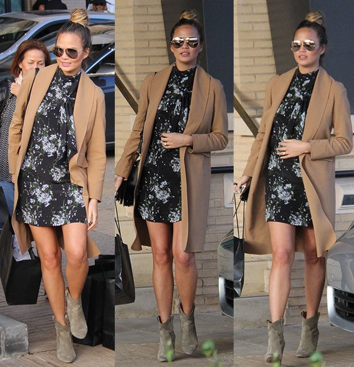 Chrissy Teigen kept herself warm with a camel coat coupled with Isabel Marant boots