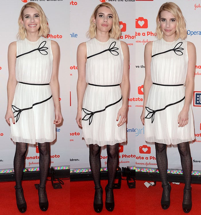 Emma Roberts poses on the red carpet in a Thakoon dress and Wolford tights