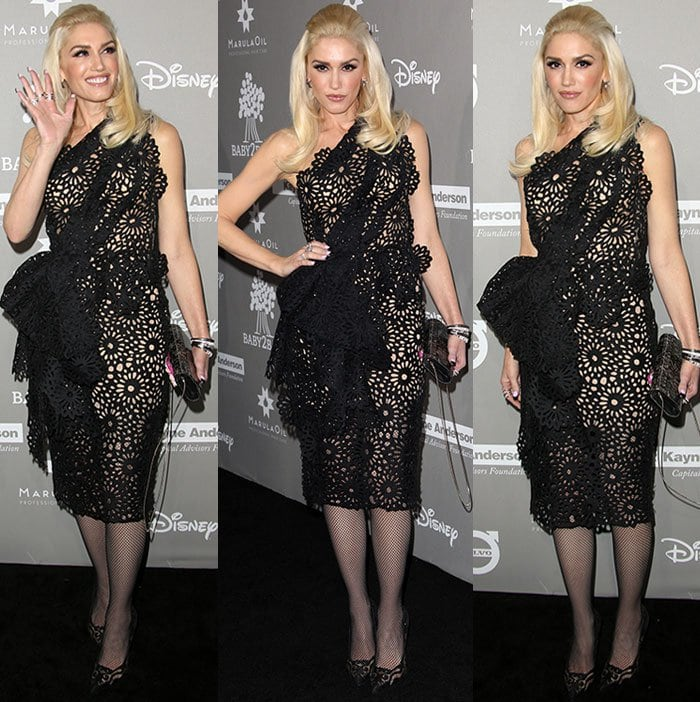 Gwen Stefani waves to the camera in a one-shouldered black dress from Marchesa