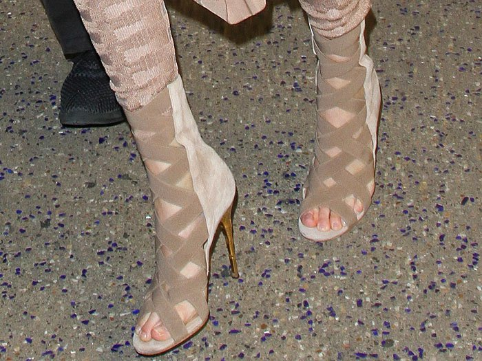 Kendall Jenner's feet in Balmain nude crisscross sandal booties with gold bamboo heels