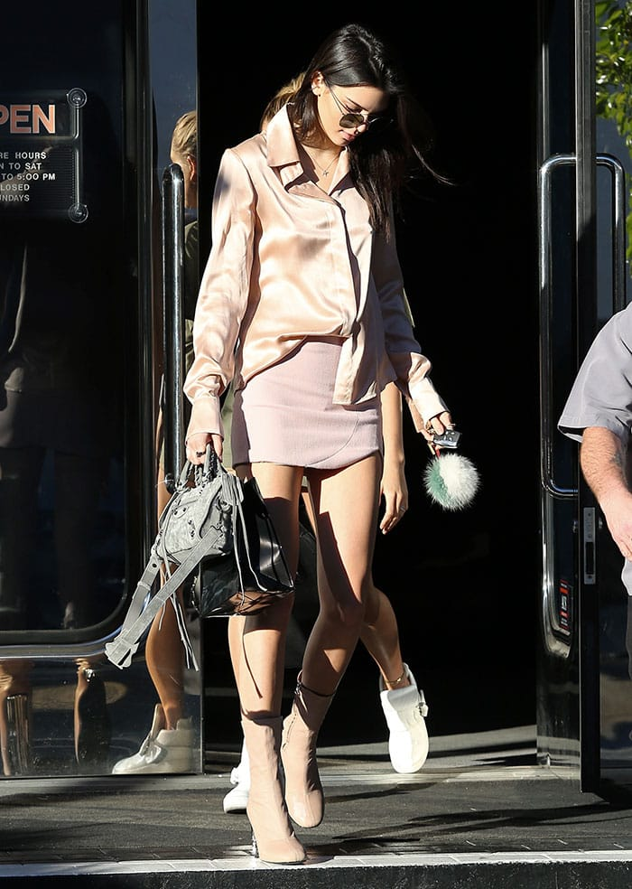 Kendall Jenner wears a pink silk blouse tucked into a pink miniskirt
