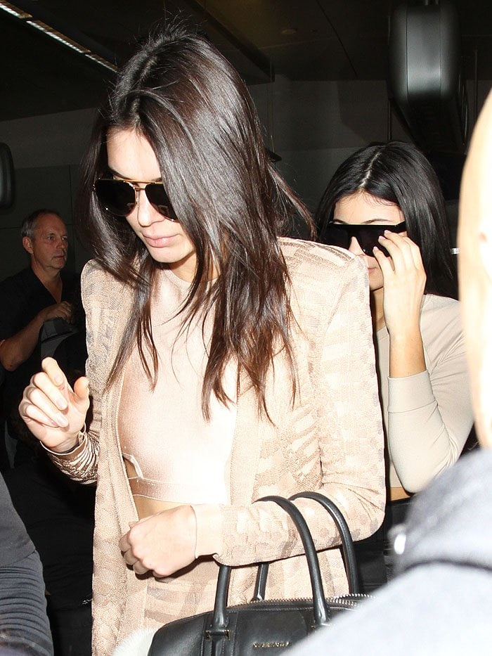 Kendall and Kylie Jenner arriving from an international flight and making their way out of LAX