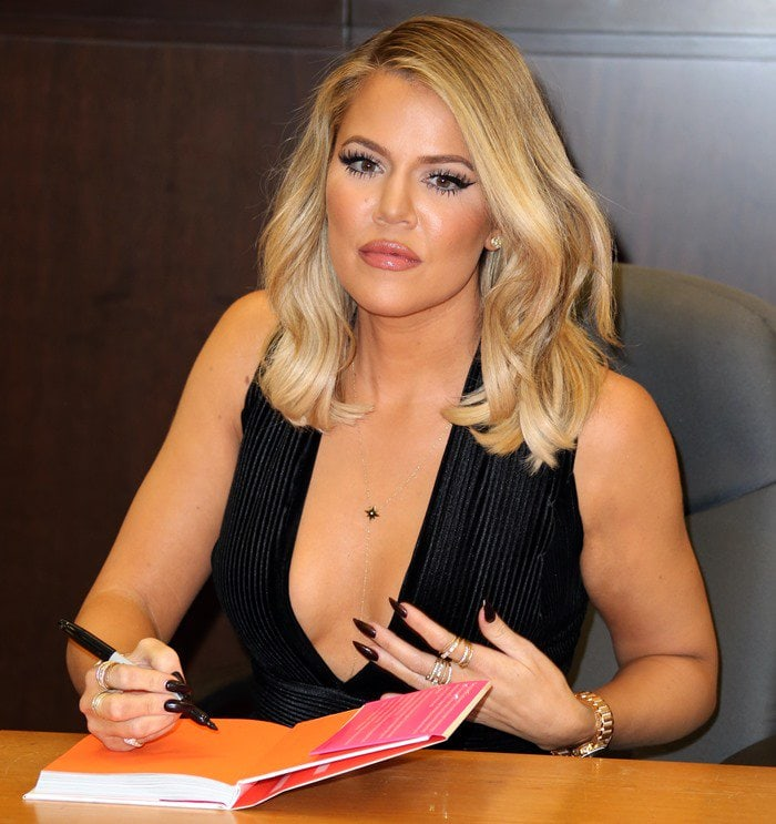 Khloé Kardashian shows off major cleavage as she signs her self-help book Strong Looks Better Naked