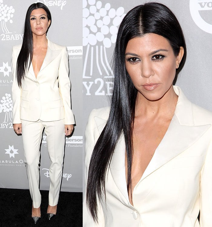 Kourtney Kardashian ditches the undergarments and shows off her cleavage in a cream pantsuit