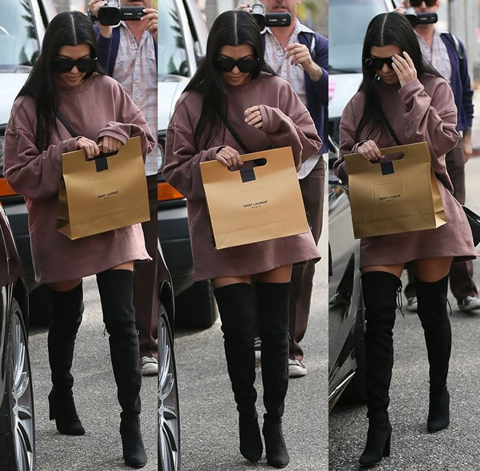 Kourtney Kardashian shields her face from the paparazzi as she walks through Los Angeles in a pair of over-the-knee boots
