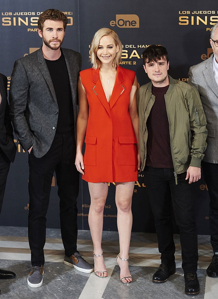 Jennifer Lawrence ensured that all eyes were on her in a bright red/orange mini dress as she was flanked by her co-stars Liam Hemsworth and Josh Hutcherson