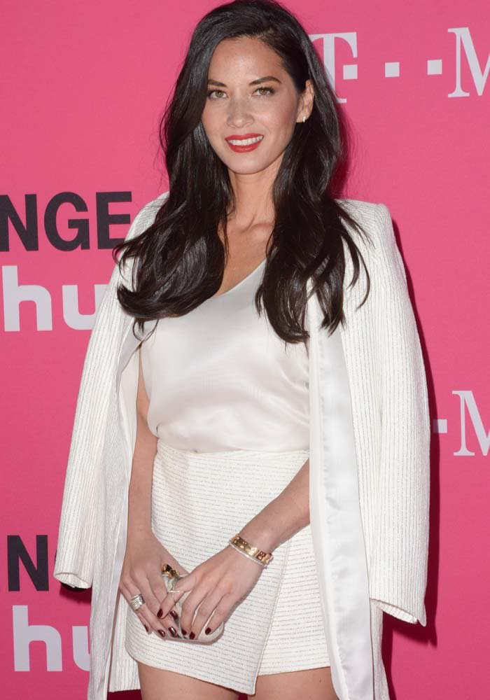 Olivia Munn holds a clutch from Kotur and wears jewelry from Ef Collection, Effy and Dana Rebecca Designs