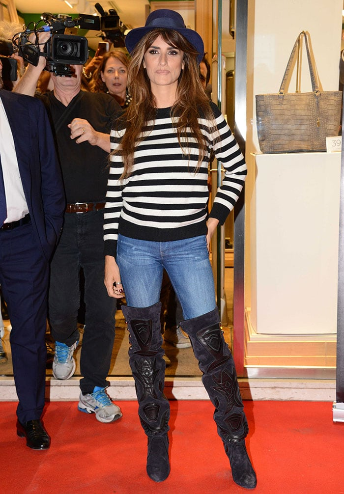 Penelope Cruz pairs a Saint Laurent sweater with skinny jeans and thigh-high boots