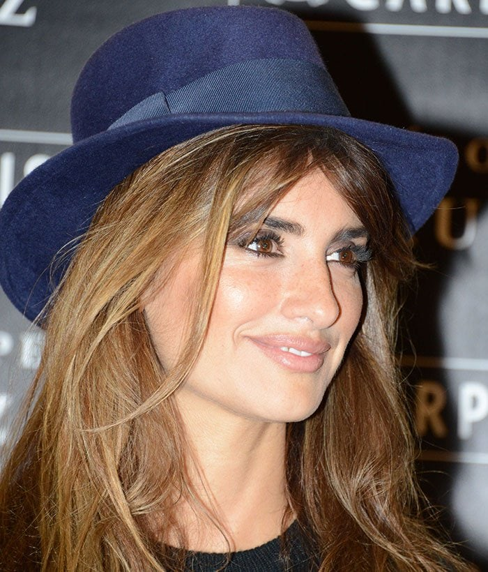 Penelope Cruz wears a hat over her hair during a photocall for Carpisa