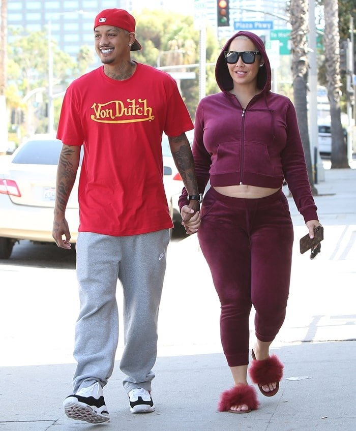 Pregnant Amber Rose wears a cropped velvet hoodie as she holds hands with her boyfriend Alexander Edwards
