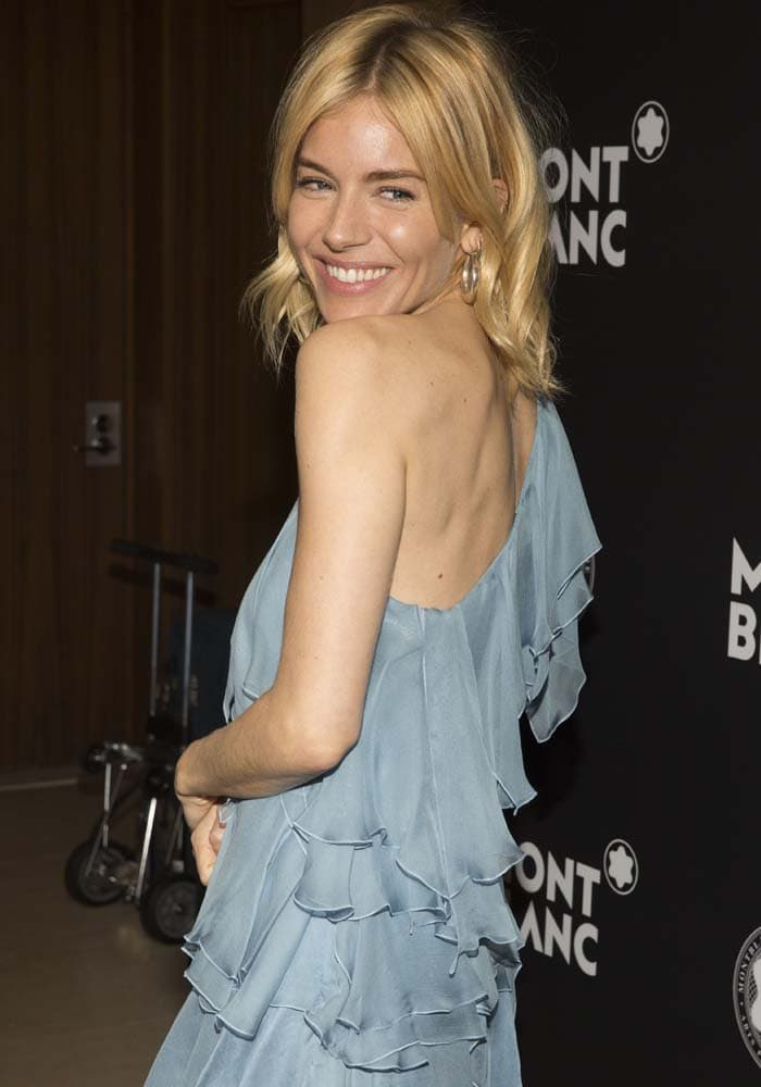 Sienna Miller throws a flirty smile over her shoulder as she poses in a ruffly dress from Saint Laurent