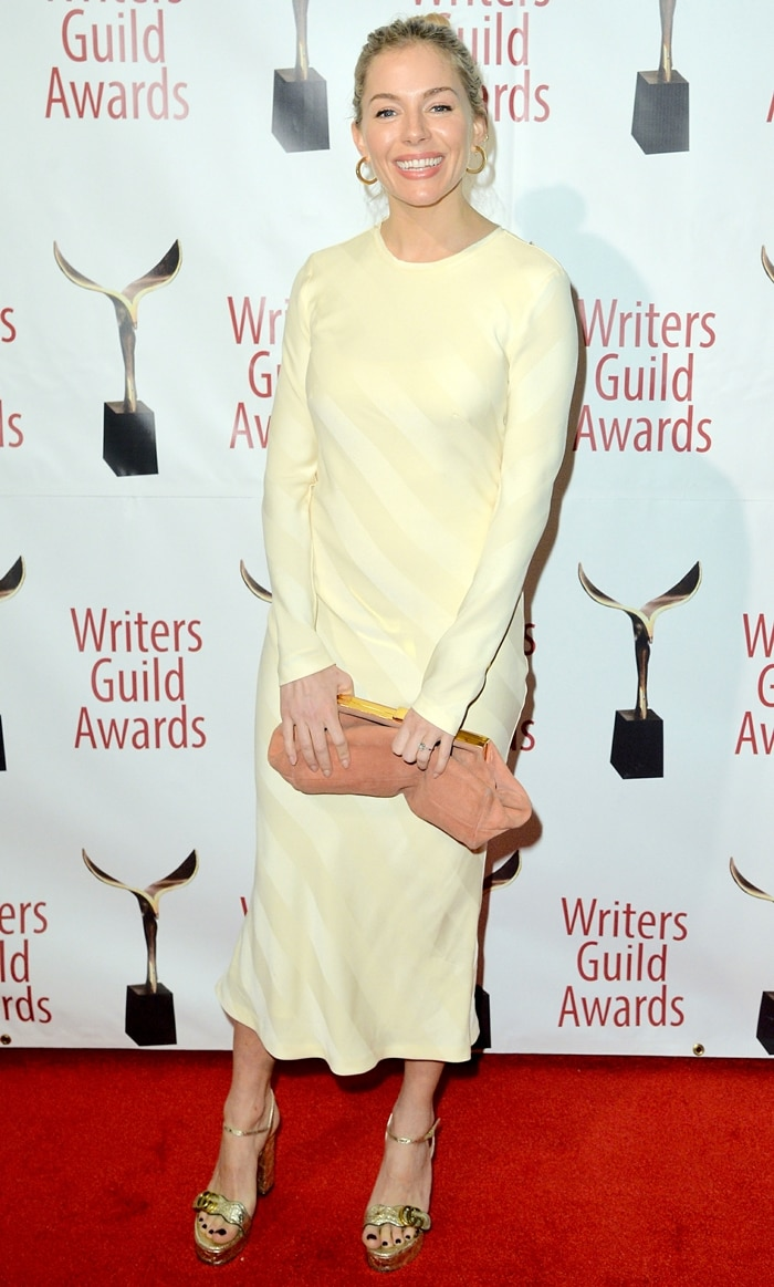 Sienna Miller wears a bow-detailed striped satin-jacquard midi dress at the 72nd Writers Guild Awards