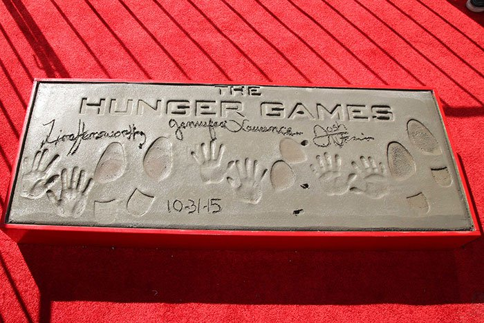 """Josh Hutcherson, Jennifer Lawrence, and Liam Hemsworth at """"The Hunger Games: Mockingjay —Part 2"""" cast hand and footprint ceremony"""