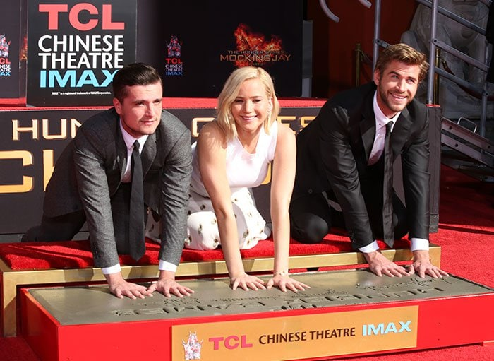 "Josh Hutcherson, Jennifer Lawrence, and Liam Hemsworth at ""The Hunger Games: Mockingjay — Part 2"" cast hand and footprint ceremony"