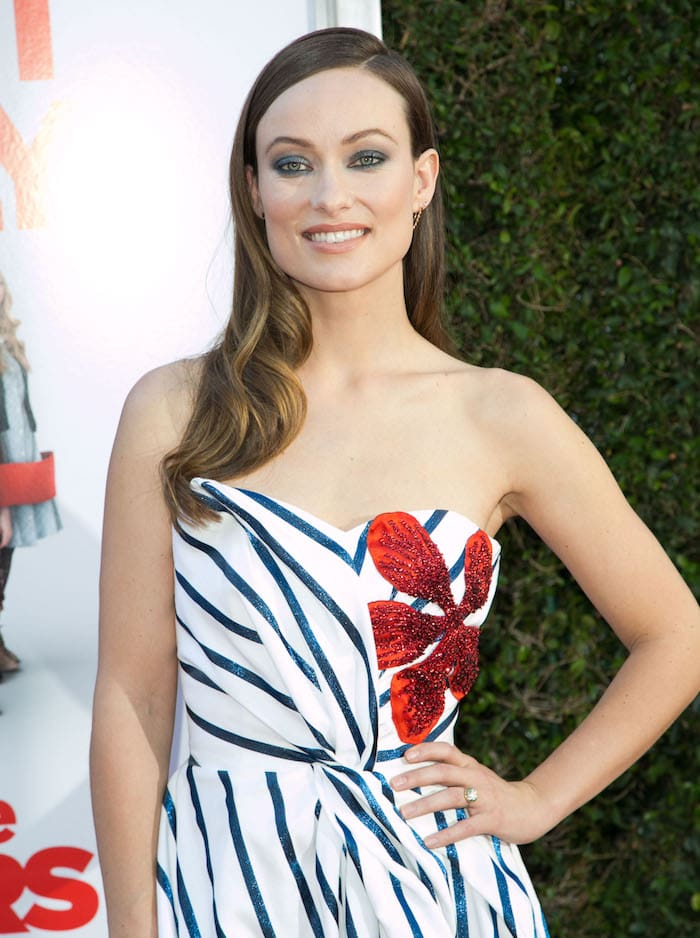 Olivia Wilde shows off the detailing on her Ingie Paris dress as she poses for photos