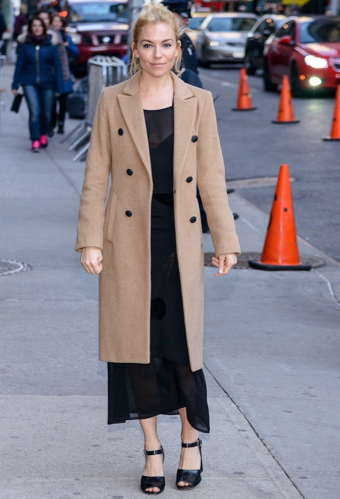 Sienna Miller wears a camel coat over a Roland Mouret dress in New York City