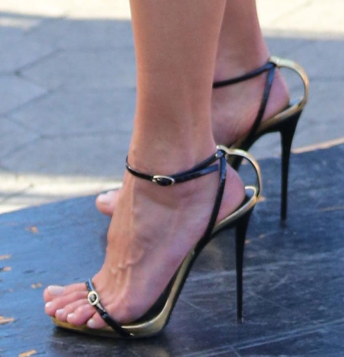 Alessandra Ambrosio shows off her toes in black-and-gold leather sandals