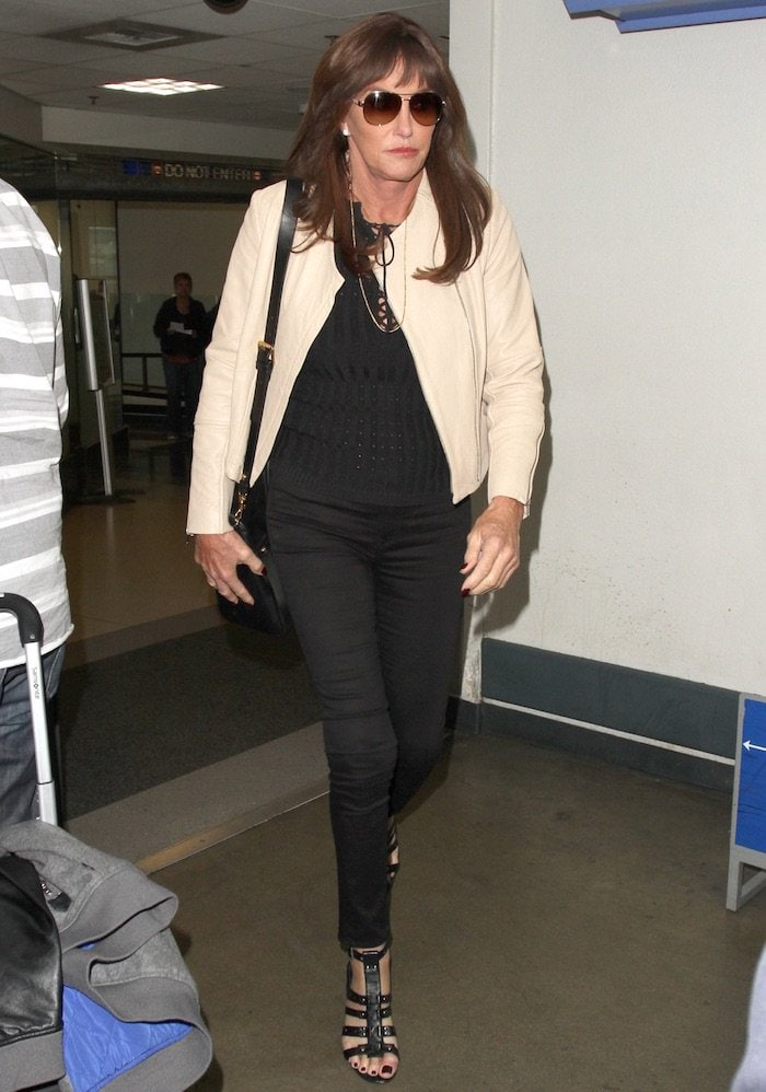 Caitlyn Jenner wears jeans and a lace-up black shirt at LAX