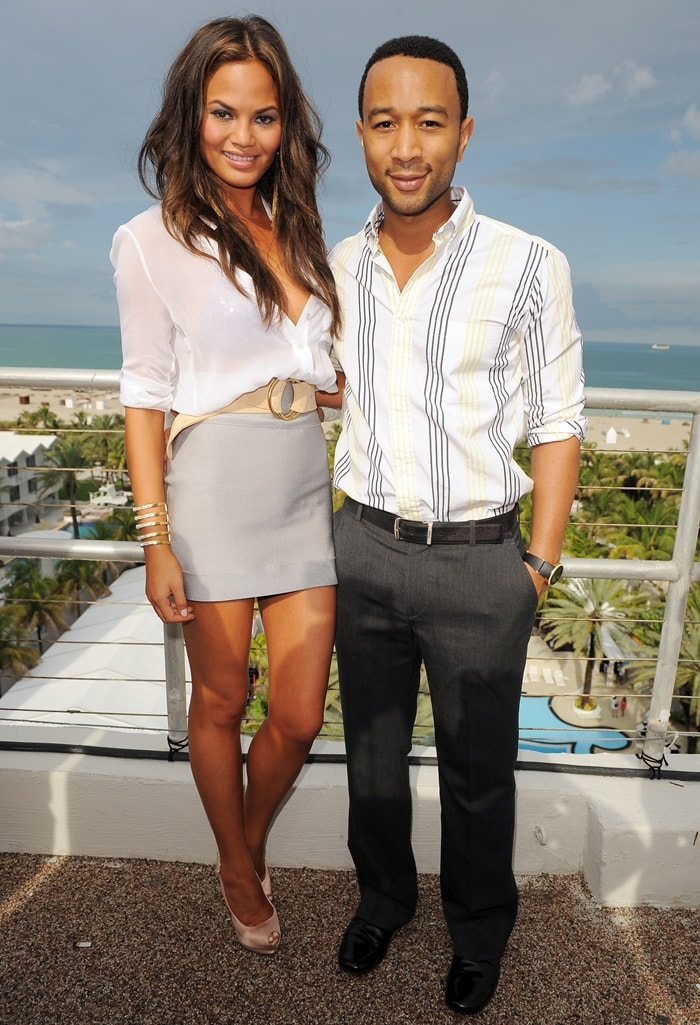 Chrissy Teigen and John Legend pose at the diNeila Brazil Press Preview