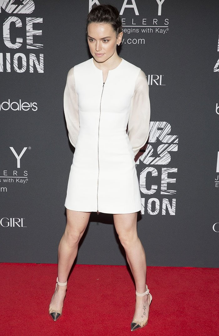 Daisy Ridley ina fitted white dress with zipper front detail and billowy sleeves