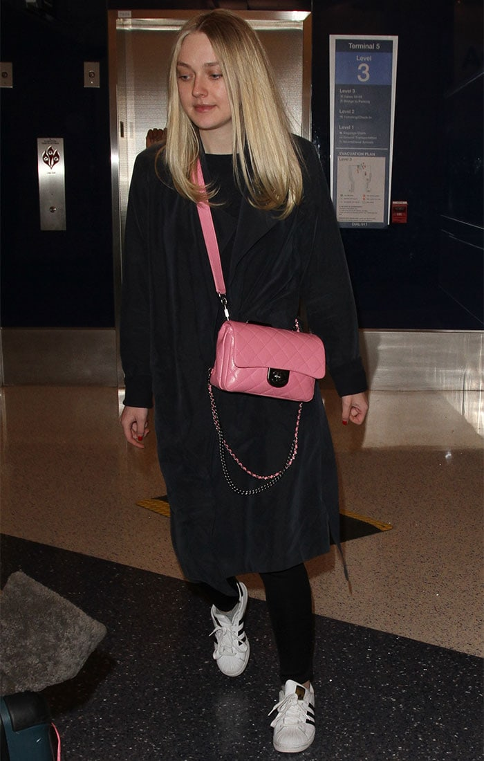 Dakota Fanning wears a long black coat over a top and pants at LAX
