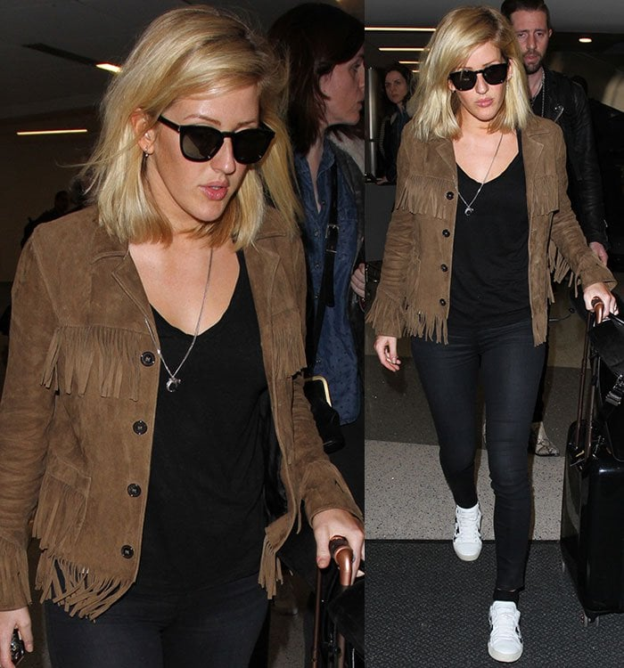 Ellie Goulding covers her eyes with a pair of dark sunglasses as she rolls her suitcase through LAX