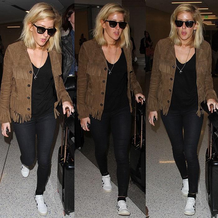 Ellie Goulding wears a brown fringe jacket over black pants and a black t-shirt