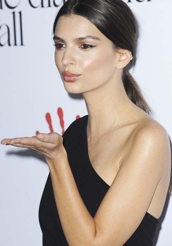 Emily Ratajkowski shows off her winged eyeliner as she blows a kiss from the red carpet