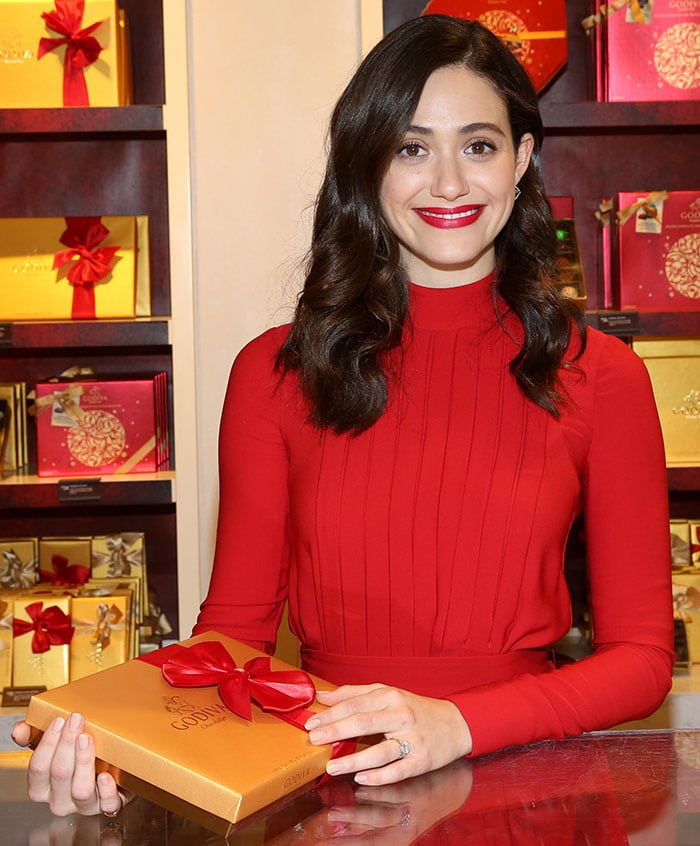 Emmy Rossum wears an all-red look from Salvatore Ferragamo that matches Godiva's Christmas packaging