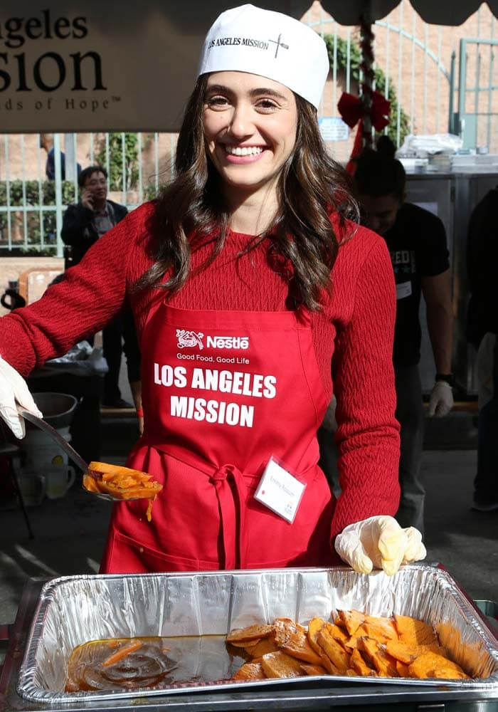 """Emmy Rossum wears a """"Los Angeles Mission"""" paper hat over her hair as she helps feed the homeless on Christmas Eve in Los Angeles"""