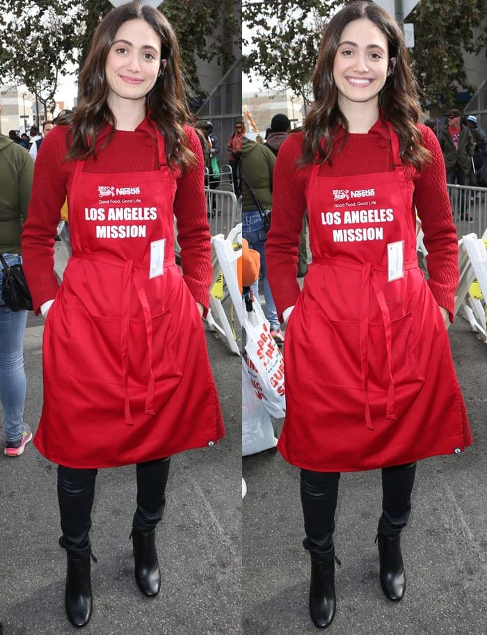 Emmy Rossum wears a red sweater underneath her LA Mission hat and apron
