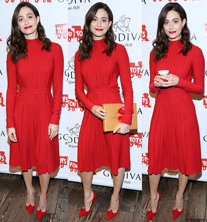 Emmy Rossum holds a box of Godiva chocolates and a cup of Godiva hot chocolate in a red pleated Salvatore Ferragamo dress