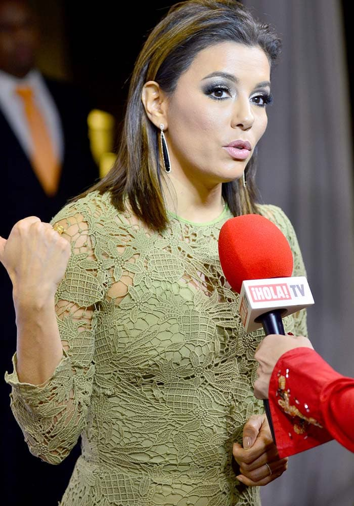 Eva Longoria wears a pale green Maria Lucia Hohan lace dress during a red carpet interview
