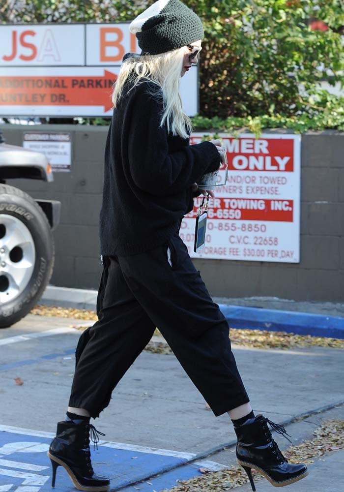 Gwen Stefani wears an all-black ensemble with a pair of L.A.M.B. booties