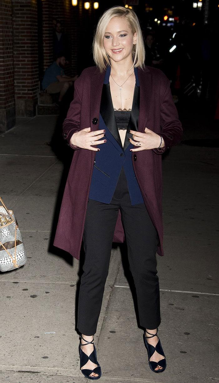 Jennifer Lawrence flashes a black bandeau bra under her wine-colored coat