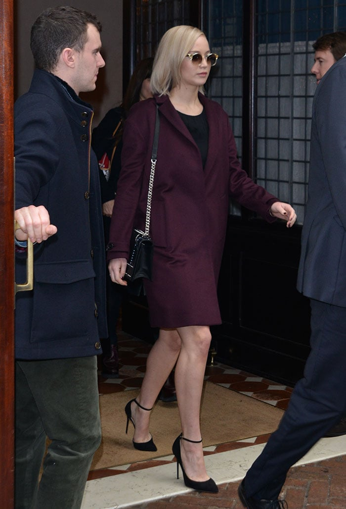Jennifer Lawrence with sleek, straight hair in an oversized burgundy cashmere coat