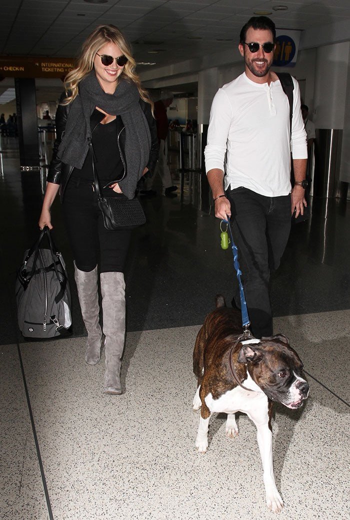 Kate Upton wears a leather jacket and a gray scarf as she catches a flight at LAX with her boyfriend Justin Verlander and their dog