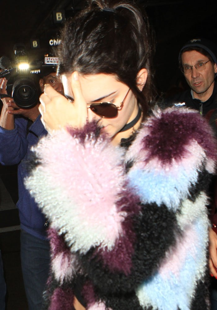 Kendall Jenner shields her face and wears her hair back as she arrives at Los Angeles International Airport